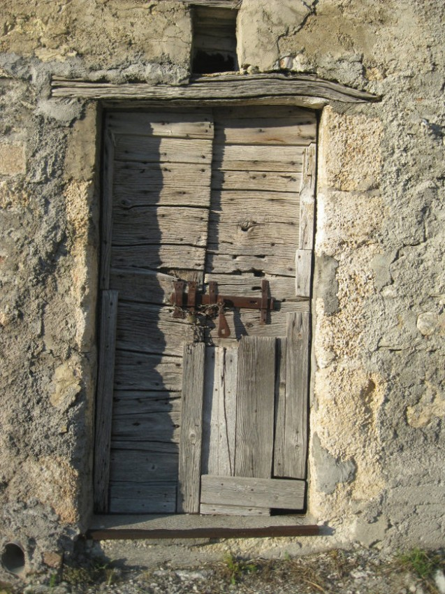 Old wooden door of an abandoned stall in Castelluccio
