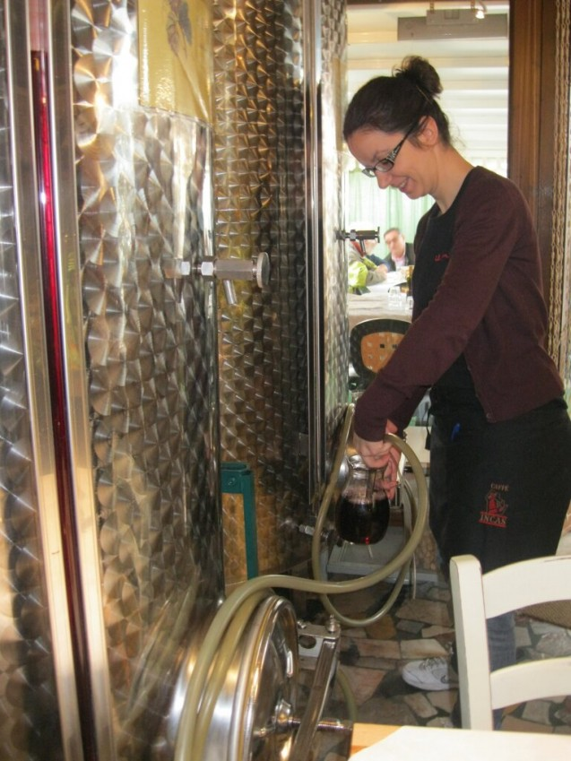 Server, Silvia, fills up wine pitchers with the hose